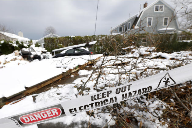 A down utility poll rests on top of a vehicle as snow covered debris from Superstorm Sandy lay in the middle of a street following a nor'easter storm, Thursday, Nov. 8, 2012, in Point Pleasant, N.J.