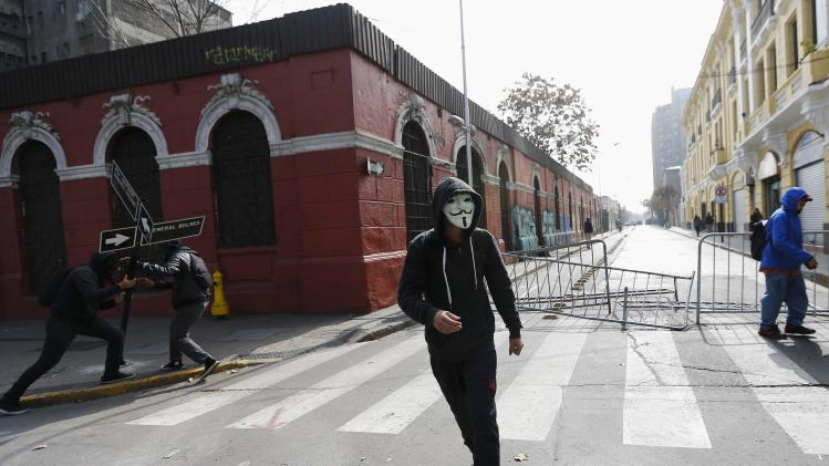 A demonstrator wearing Guy Fawkes masks attends demonstration against government to demand changes in education system in Santiago