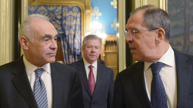 CAPTIONS ADDS IDENTITY OF MAN IN CENTRE OF PHOTO Russian Foreign Minister Sergey Lavrov, right, and his Egyptian counterpart Mohamed Kamel Amr, left, walk prior to a meeting in Moscow on Friday, Dec. 28, 2012. Russian deputy foreign minister Gennady Gotilov is in background centre.  (AP Photo)