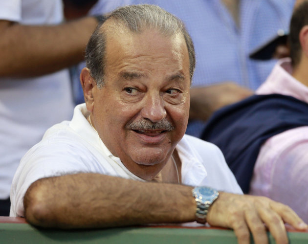 In this Aug. 7, 2011 file photo, Mexican businessman Carlos Slim sits in the stands before a baseball game in Boston. The Mexican tycoon said Saturday, Nov. 17, 2012, that he will invest 2.5 billion d
