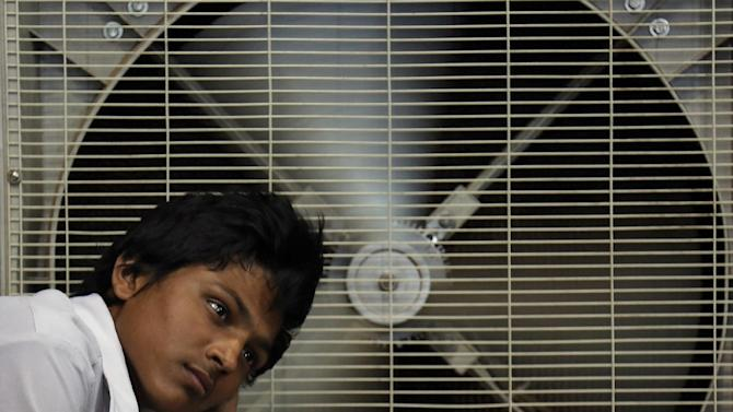 FILE - In this May 31, 2015 file photo, an Indian man rests in front of an air cooler to cool himself on a hot summer day in Hyderabad, in the southern Indian state of Telangana. Because of man-made global warming and a strong El Nino, Earth's wild weather this year is bursting the annual heat record, the World Meteorological Organization announced Wednesday. (AP Photo/Mahesh Kumar A., File)