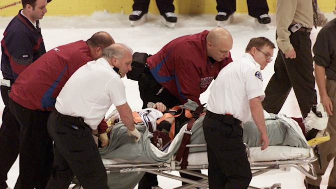 In this March 8, 2004, file photo, Colorado Avalanche NHL hockey player Steve Moore is taken off the ice by medical staff  after he was hit by Vancouver Canucks'  Todd Bertuzzi during the third period of NHL action in Vancouver, British Columbia. A settlement has been reached in Moore's lawsuit against Bertuzzi for his career-ending hit during an NHL game 10 years ago