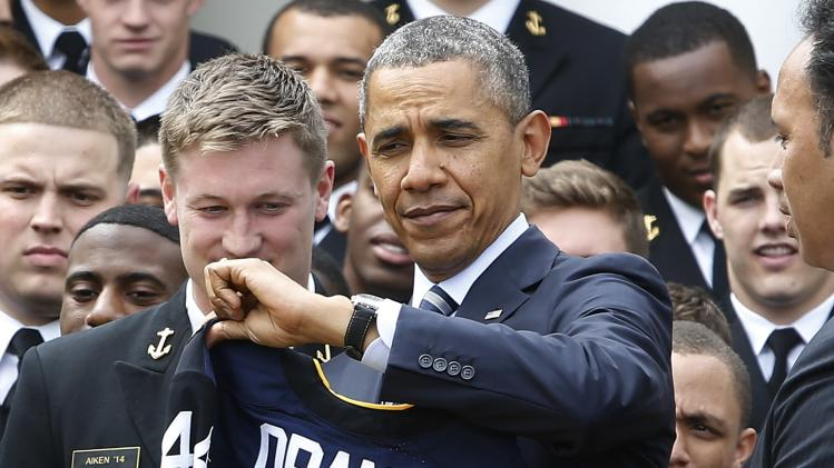 U.S. President Obama receives U.S. Naval Academy football jersey from team captain Aiken after Obama presented the Commander-in-Chief Trophy to the team in Rose Garden at the White House in Washington