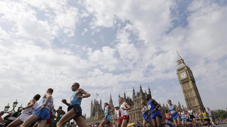 Athletes run near Big Ben during the men's marathon at the 2012 Summer Olympics in London, Sunday, Aug. 12, 2012. (AP Photo/Luca Bruno)