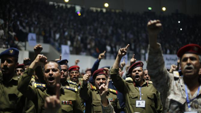 Army and police officers loyal to the Houthi movement shout slogans during a gathering in Sanaa