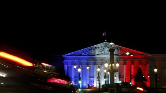 Evening traffic makes its way across the Place de la Concorde towards the National Assembly that is lit in the blue, white and red colors of the French flag in central Paris