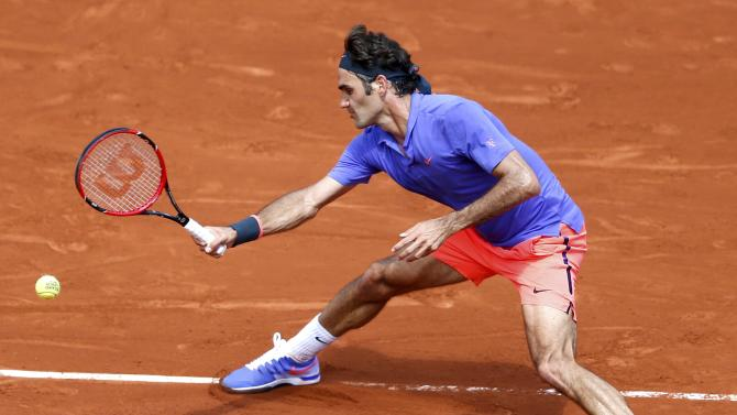 Roger Federer of Switzerland plays a shot to Marcel Granollers of Spain during their men's singles match at the French Open tennis tournament at the Roland Garros stadium in Paris