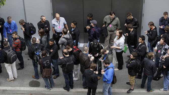 People wait in line outside the Moscone West Center for the start of the Apple Worldwide Developers Conference, Monday, June 10, 2013, in San Francisco. (AP Photo/Eric Risberg)