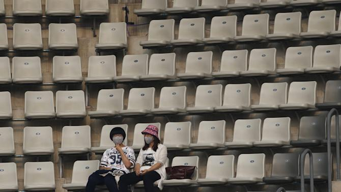 Spectators wearing masks watch men's singles match between David Goffin of Belgium and Andreas Seppi of Italy, on a polluted day at the China Open tennis tournament in Beijing