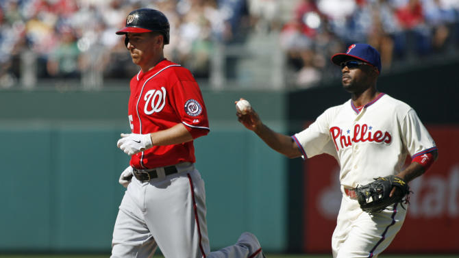 Washington Nationals' Adam LaRoche, left, is tagged out by by Philadelphia Phillies' Jimmy Rollins in a rundown in the seventh inning of a baseball game on Sunday, Aug. 26, 2012, in Philadelphia. The Phillies won 4-1. (AP Photo/H. Rumph Jr)