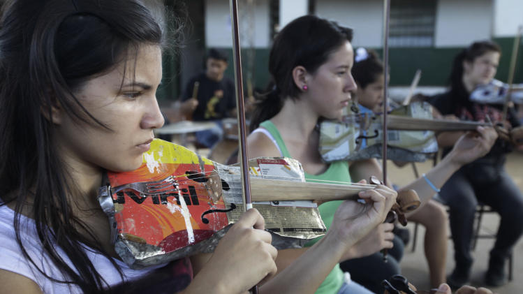 "In this Dec. 11, 2012 photo, Ana Meza, 16, plays a violin made of recycled materials as she attends a practice session with ""The Orchestra of Instruments Recycled From Cateura""  in Cateura, a vast landfill outside Paraguay's capital of Asuncion, Paraguay.  After years of practice, the youngsters of ""The Orchestra of Instruments Recycled From Cateura"" have begun to perform internationally, with sponsors paying their way to places like Brazil, Panama and Colombia.  They hope to play at an exhibit opening next year in their honor at the Musical Instrument Museum in Phoenix, Arizona. (AP Photo/Jorge Saenz)"