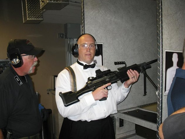 "This July 28, 2012 photo provided by Bob MacDuff shows MacDuff holding an automatic weapon at the Gun store in Las Vegas after his ""shotgun wedding."" One Las Vegas shooting range is selling ""take a sh"