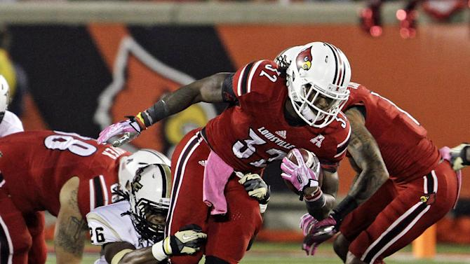 Louisville running back Senorise Perry (32) gets pulled down from behind by Central Florida's Clayton Geathers (26) on a first-quarter run during an NCAA college football game in Louisville, Ky., Friday, Oct. 18, 2013. (AP Photo/Garry Jones)