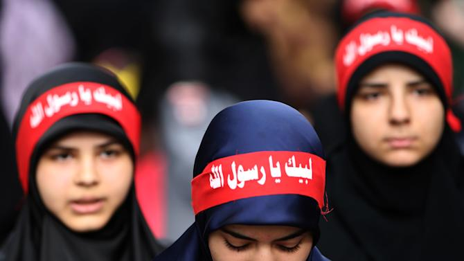"""In this picture taken on Monday Sept. 17, 2012, Hezbollah veiled women wear Arabic headbands that read, """"at your service God's prophet,"""" during a rally denouncing an anti-Islam film that has provoked a week of unrest in Muslim countries worldwide, in the southern suburb of Beirut, Lebanon. The vast majority of Muslims have not taken to the streets over a film mocking the Prophet Muhammad, and behind the visible public anger a more measured debate is taking place over how much free speech is acceptable in the Muslim world. While many do yearn for more openness, few if any will go as far as accepting the right to blaspheme as the ultimate test of freedom of speech.(AP Photo/Hussein Malla)"""