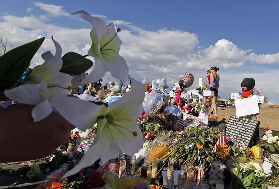 "A woman holds flowers before placing them at the memorial across from the movie theater, Wednesday, July 25, 2012 in Aurora, Colo. Twelve people were killed and over 50 wounded in a shooting attack early Friday at the packed theater during a showing of the Batman movie, ""The Dark Knight Rises."" (AP Photo/Alex Brandon)"