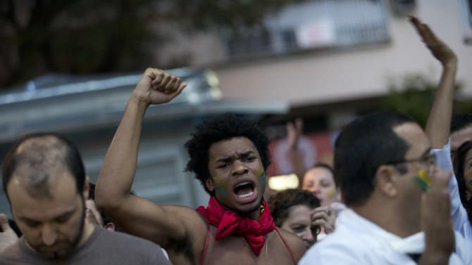A man shouts slogans during an anti-government protest in the Ipanema neighborhood, in Rio de Janeiro, Brazil, Friday, June 21, 2013. The country's president, who is a former leftist guerrilla, has done little more than show brief support for the protesters since the demonstrations began a week ago. That's brought criticism that she has allowed the situation to spiral out of control. Rousseff was to meet Friday with bishops from the Catholic Church about the possible impact of the protests on a papal visit that is still scheduled next month. (AP Photo/Silvia Izquierdo)