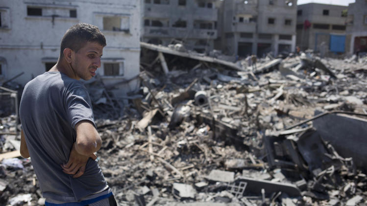 A Palestinian inspects a destroyed house in the heavily bombed Gaza City neighborhood of Shijaiyah, close to the Israeli border, Friday, Aug. 1, 2014. A three-day Gaza cease-fire that began Friday quickly unraveled, with Israel and Hamas accusing each other of violating the truce as several Palestinians were killed in a heavy exchange of fire in the southern town of Rafah. (AP Photo/Dusan Vranic)