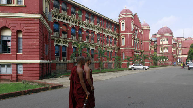 In this photo taken on June 1, 2012, Myanmar Buddhist monks walk on a road near Yangon Hospital in downtown Yangon, Myanmar. There's nowhere else in Asia like it any more: Yangon's cityscape is filled with colonial buildings and colorful multiethnic communities, bypassed by the rapid modernization that's bulldozed the past elsewhere. Now, as Myanmar opens its long-closed doors to the outside world, including tourists, an effort is under way to preserve Yangon's architecture and atmosphere from development and decay.  (AP Photo/Khin Maung Win)