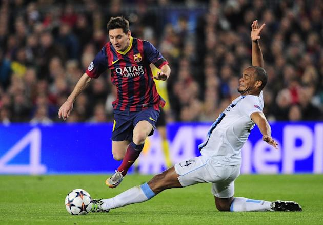 Barcelona's Lionel Messi, left, takes the ball past Manchester City's Vincent Kompany during a Champions League, round of 16, second leg, soccer match between FC Barcelona and Manchester City