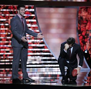 Denver Broncos' Tim Tebow reacts after correcting Alec Baldwin on his Tebowing form during the inaugural NFL Honors show Saturday, Feb. 4, 2012, in Indianapolis.The New York Giants will face the New England Patriots in the NFL football's Super Bowl XLVI in Indianapolis on Feb. 5. (AP Photo/Marcio Sanchez)