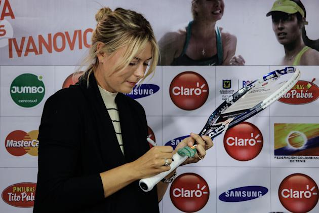BOGOTA, Dec. 6, 2013 (Xinhua/IANS) -- Russia's tennis player Maria Sharapova, signs a racket during a press conference in Bogota city, Colombia, on Dec. 5, 2013. Tennis players Maria Sharapova and