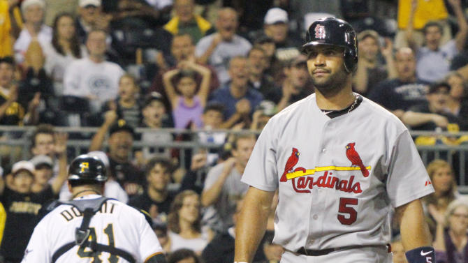 St. Louis Cardinals' Albert Pujols (5) walks back and Pittsburgh Pirates catcher Ryan Doumit, rear left, head their dugouts after Pujols was called out on strikes with two men on base for the Cardinals last out of the seventh inning of a baseball game on Monday, Aug. 15, 2011, in Pittsburgh. The Pirates won 6-2. (AP Photo/Keith Srakocic)