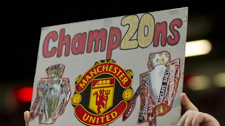 A Manchester United supporter holds a sign as the team celebrates winning their 20th English Premier League title after their 3-0 win over Aston Villa in their soccer match at Old Trafford Stadium, Manchester, England, Monday April 22, 2013. (AP Photo/Jon Super)