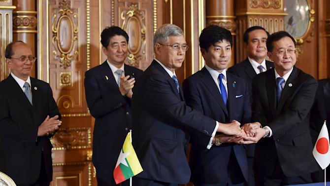 Representatives from Japan, Myanmar, and Thailand shakes hands each other during the signing ceremony on Dawei port project at the Akasaka State Guest House in Tokyo