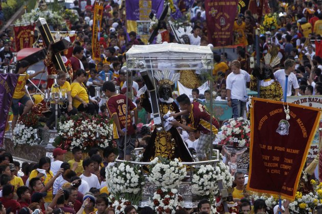 Devotees participate in a procession of replica statues of the Jesus of the Black Nazarene along a street in Manila January 7, 2013. Authorities are in full alert as millions of devotees are expected to attend the grand procession of the Jesus of the Black Nazarene on Wednesday.    REUTERS/Romeo Ranoco (PHILIPPINES - Tags: SOCIETY RELIGION)