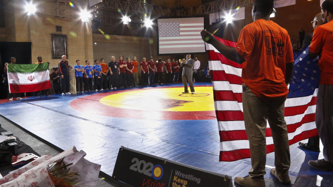 """Trumpeter Joey Morant plays the U.S. national anthem as the U.S. and Iran teams gather on the mat to start competition in an exhibition wrestling match at Grand Central Terminal, Wednesday, May 15, 2013, in New York. """"The Rumble on the Rails""""  exhibition, featuring teams from the United States, Iran and Russia, raises money for charity but is also aimed at drawing attention to the sport's attempt to stay in the Olympics. (AP Photo/Bebeto Matthews)"""