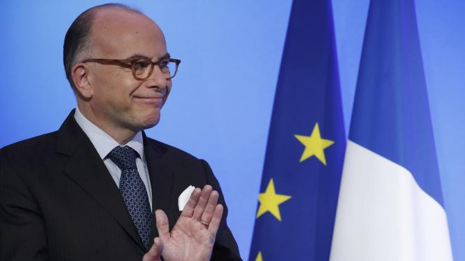 French Prime Minister Bernard Cazeneuve applauds after he delivered his New Year address to the press at the Hotel Matignon in Paris