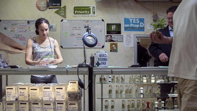 In this photo taken Tuesday, May 14, 2013, Nicole Denis, left, and Brennan Thicke, help fill medical marijuana prescriptions at the Venice Beach Care Center medical marijuana dispensary in Venice, Calif. Los Angeles politicians have tried and failed for so long to regulate medical marijuana that it was only a matter of time before voters got a chance to control shops that have proliferated. (AP Photo/Damian Dovarganes)