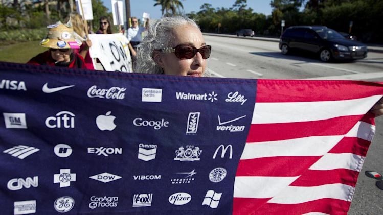 Karen Levin, carrying an American flag with corporate logos, protests Wal-Mart in Boynton Beach, Fla., Friday, Nov 23, 2012. Wal-Mart employees and union supporters are taking part in today's nationwide demonstration for better pay and benefits A union-backed group called OUR Walmart, which includes former and current workers, was staging the demonstrations and walkouts at hundreds of stores on Black Friday, the day when retailers traditionally turn a profit for the year. (AP Photo/J Pat Carter)