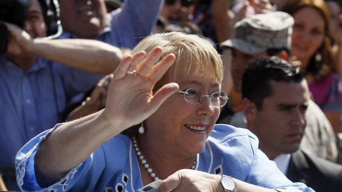 Presidential candidate and former President Michelle Bachelet waves to supporters after casting her vote during presidential elections in Santiago, Chile, Sunday, Dec. 15, 2013. Michelle Bachelet is widely expected to return to Chile's presidency by beating conservative rival Evelyn Matthei in Sunday's runoff vote. (AP Photo/Luis Hidalgo).