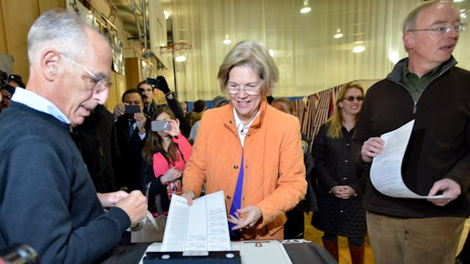 Democratic candidate for Sennate Elizabeth Warren, center, casts her ballot as she and her husband , Bruce Mann, right, visited the polls near their Cambridge, Mass. home on  Election Day, Tuesday, Nov. 6, 2012. Warren is running against Sen. Scott Brown (R-MA), who was elected in a special election in 2010 after the death of Sen. Ted Kennedy (D-MA).  (AP Photo/Josh Reynolds)