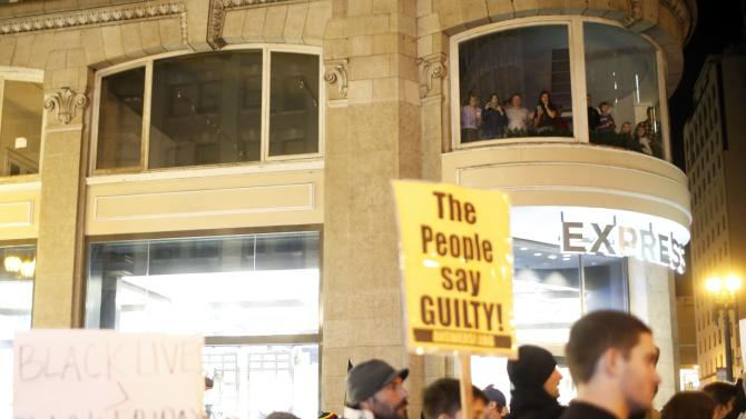 Onlookers watch from a building during a demonstration against a grand jury's decision in the Ferguson, Missouri shooting of Michael Brown in San Francisco