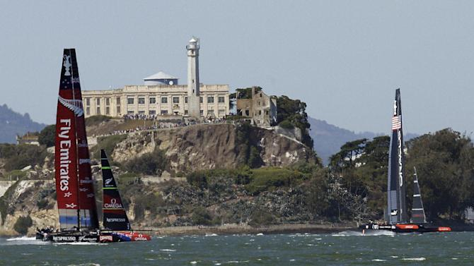 Emirates Team New Zealand, left, and Oracle Team USA pass Alcatraz Island during the 11th race of the America's Cup sailing event Wednesday, Sept. 18, 2013, in San Francisco. (AP Photo/Ben Margot)