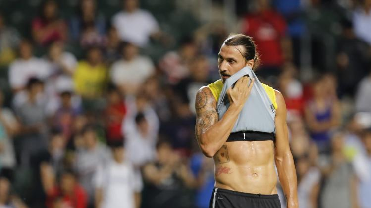 Paris Saint-Germain soccer player Zlatan Ibrahimovic wipes his face during a training session in Hong Kong