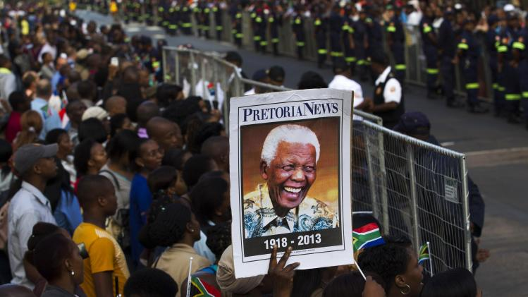 People wait for the cortege carrying the coffin of former South African President Mandela to pass by the city center of Pretoria