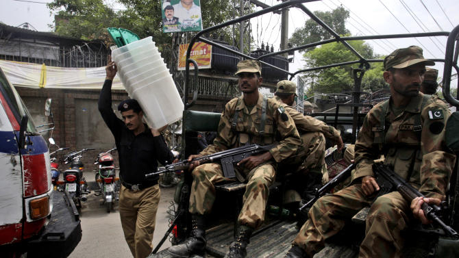 Pakistani army soldier, guard outside the city court, as a policeman carries ballot boxes to polling stations, in Lahore, Pakistan, Friday, May 10, 2013. Pakistan is scheduled to hold parliamentary elections on May 11, the first transition between democratically elected governments in a country that has experienced three military coups and constant political instability since its creation in 1947. The parliament's ability to complete its five-year term has been hailed as a significant achievement. (AP Photo/K.M. Chaudary)