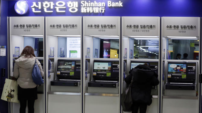 Customers use the automated teller machine at a branch of Shinhan Bank in Seoul, South Korea, Thursday, March 21, 2013. Investigators have traced a coordinated cyberattack that paralyzed tens of thousands of computers at six South Korean banks and media companies to a Chinese Internet Protocol address, authorities in Seoul said Thursday. (AP Photo/Lee Jin-man)