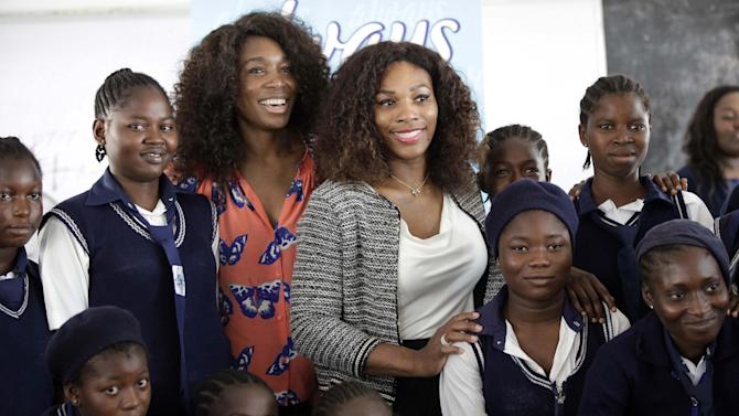 """US tennis players Venus Williams, centre left, and Serena Williams, centre right, pose for a photographs with school girls, during a visit to Lagos, Nigeria, Thursday, Nov. 1, 2012. On their first visit to Nigeria, Serena and Venus Williams want to inspire local kids to set their goals high. We were really able to break the mold and win a lot of Grand Slams and a lot of tournaments and not only that, but kind of change the face of tennis,"""" Serena said Wednesday before an exhibition match against her sister in Lagos on Friday. (AP Photo/Sunday Alamba)"""