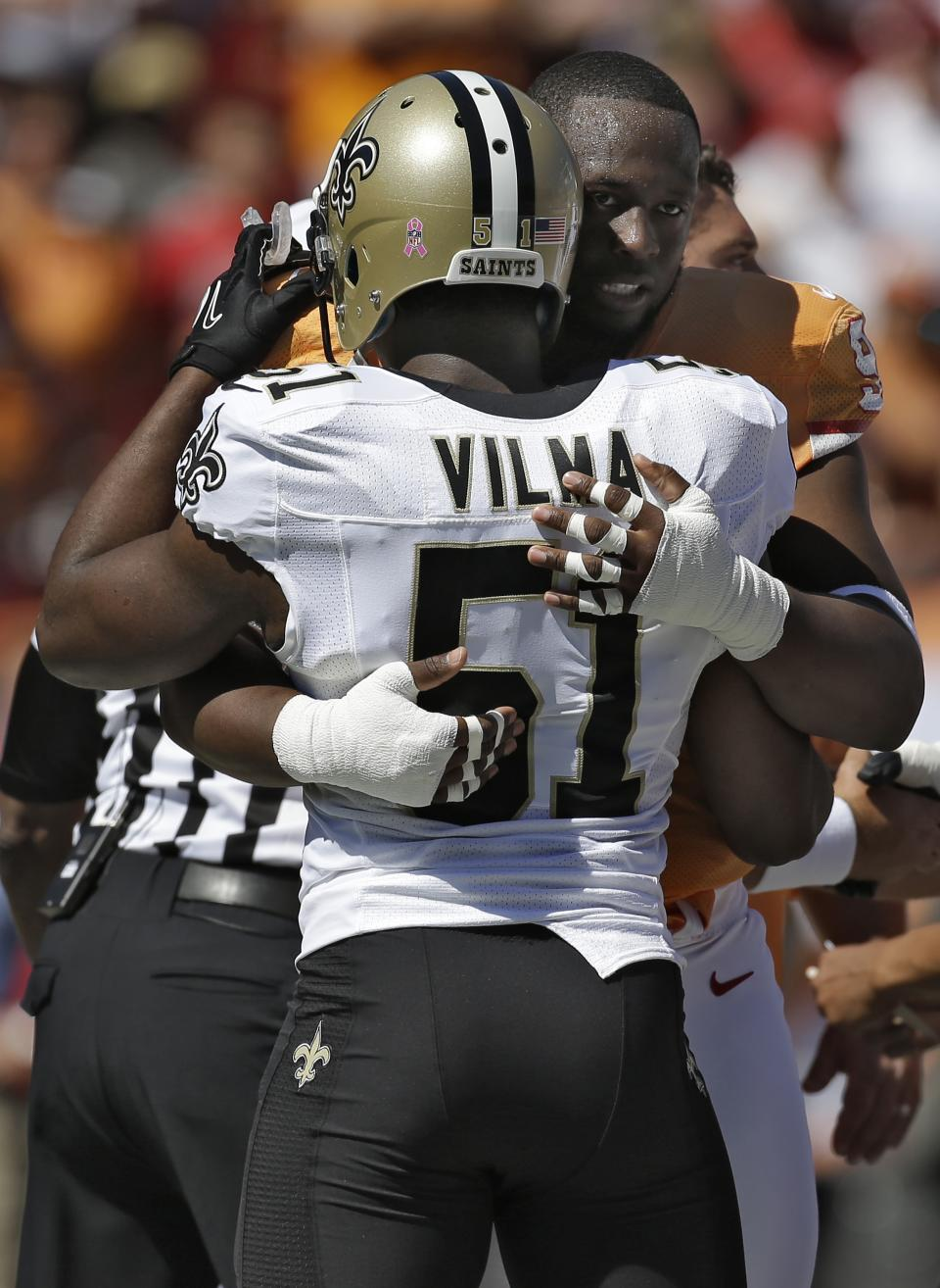 New Orleans Saints linebacker Jonathan Vilma (51) gets a hug from Tampa Bay Buccaneers defensive tackle Gerald McCoy (93) after the coin flip before an NFL football game Sunday, Oct. 21, 2012, in Tampa, Fla. (AP Photo/Chris O'Meara)