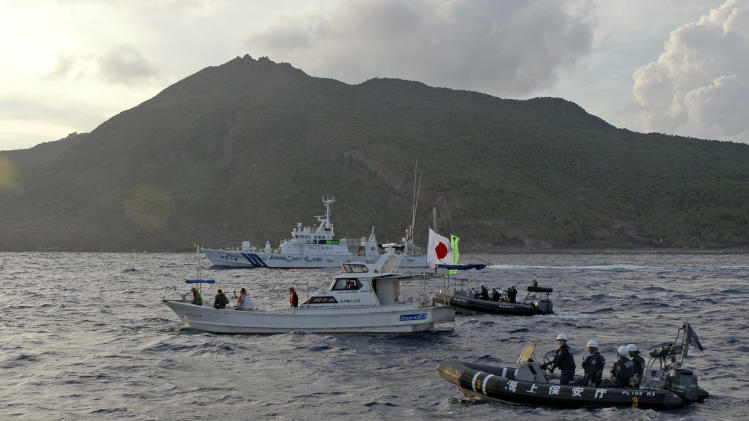 Japanese Coast Guard vessel and boats, rear and right, sail alongside Japanese activists' fishing boat, center with a flag, warning the activists away from a group of disputed islands called Diaoyu by China and Senkaku by Japan, early Sunday, Aug. 18, 2013. Nearly two dozen Japanese nationalist activists and fishermen have sailed to a small group of islands at the center of a territorial dispute with China. They were closely monitored by Japan's Coast Guard, but there were no Chinese patrols in the area and no incidents were reported. (AP Photo/Emily Wang)