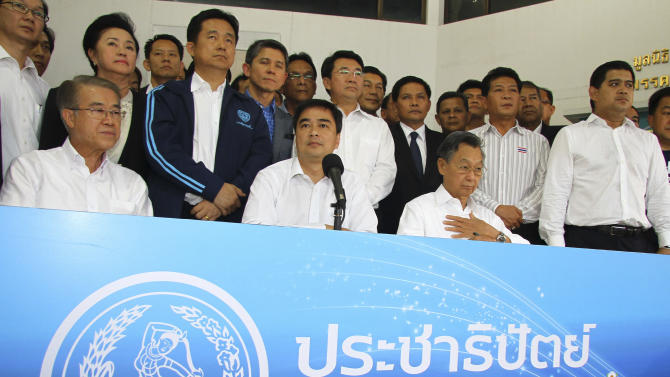 Leader of Thailand's Democrat Party and former Prime Minister Abhisit Vejjajiva, sitting center, listens to a question during a news conference with senior party's members Banyat Bantattan, sitting left, and former Prime Minister Chuan Leekpai, sitting right, along with other members in Bangkok, Thailand Sunday, Dec. 21, 2013. Thailand's main opposition Democrat Party said Saturday that it would boycott February's general election, deepening the country's weeks-long political crisis. (AP Photo)
