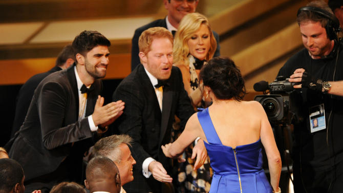 "Gail Mancuso accepts the award for outstanding directing for a comedy series for her work on ""Modern Family"" at the 66th Annual Primetime Emmy Awards at the Nokia Theatre L.A. Live on Monday, Aug. 25, 2014, in Los Angeles. Looking on from left are Justin Mikita, Jesse Tyler Ferguson and Julie Bowen. (Photo by Chris Pizzello/Invision/AP)"