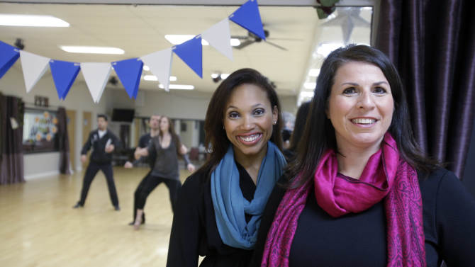 In this Tuesday, Sept. 30, 2014 photo, Fred Astaire Dance Studio owner Andrea Bisconti, right, poses on the dance floor with instructor Kellie Love, in Willoughby, Ohio. Faced with the prospect of losing Love, who wanted to start her own studio, Bisconti made her a business partner. They are now negotiating to take over a studio that's up for sale. (AP Photo/Mark Duncan)