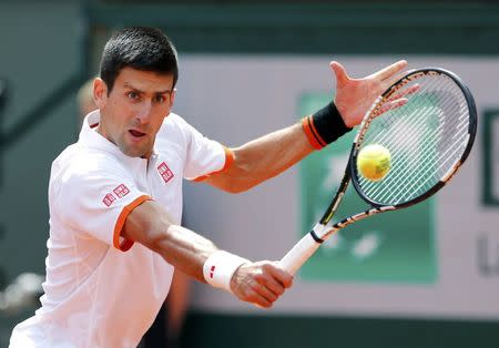 Novak Djokovic of Serbia plays a shot to Thanasi Kokkinakis of Australia during their men's singles match at the French Open tennis tournament at the Roland Garros stadium in Paris