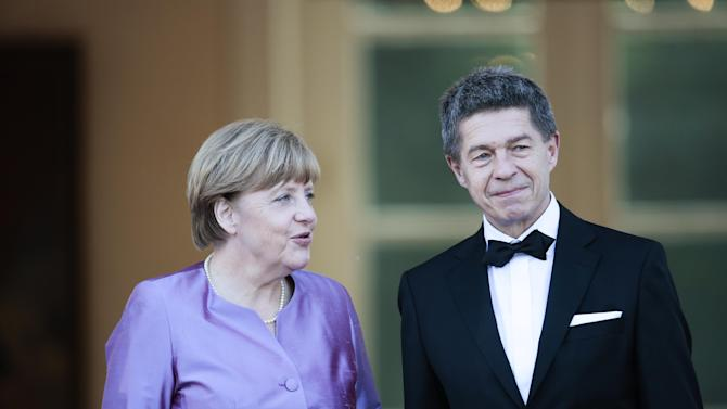 German Chancellor Angela Merkel, left, and her husband Joachim Sauer arrive for an official state dinner for Britain's Queen Elizabeth II, in front of Germany's President Joachim Gauck's residence, Bellevue Palace, in Berlin, Wednesday, June 24, 2015. (AP Photo/Markus Schreiber)