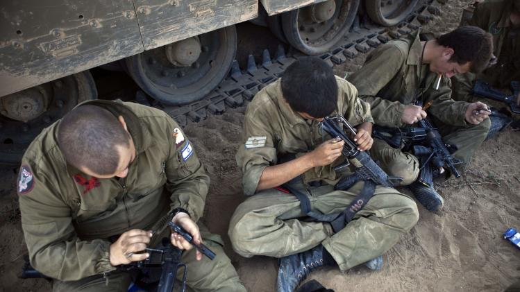 Israeli soldiers clean their weapons at a staging area near border with the Gaza Strip